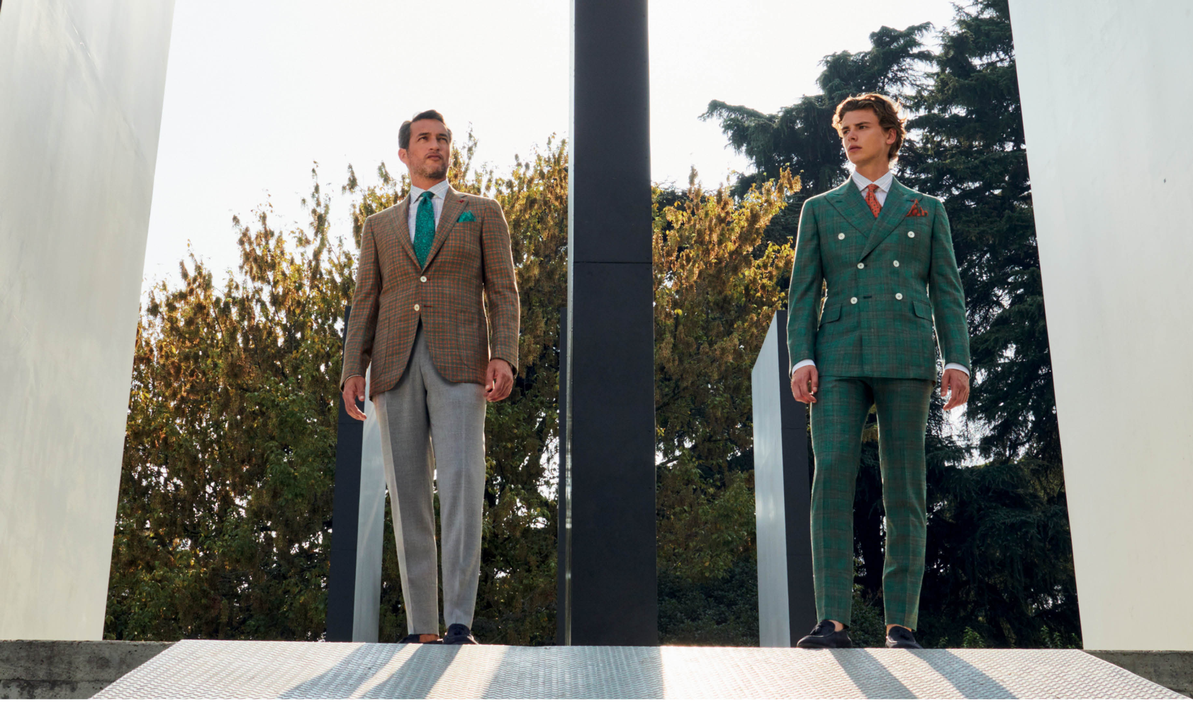 Men on the left is wearing a beige sport jacket, green tie and grey trousers. Men on the right is wearing a green double breasted suit with a red tie